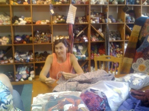Maggie, the owner of Ewenique Yarns, surrounded by fiber